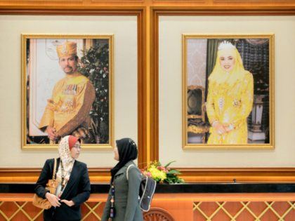Two woman walk past portraits of Brunei Sultan Hassanal Bolkiah (L) and Queen Saleha (R) at the prime minister's complex in Bandar Seri Begawan on April 24, 2013 ahead of the start of the Association of Southeast Asian Nations (ASEAN) summit. Southeast Asian leaders are meeting in Brunei hoping to …
