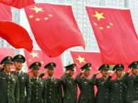 This photo taken 03 October, 2007 shows military officers saluting for a group photo beneath a display of national flags at a park in Beijing. China's ruling Communist Party's five-yearly gathering, it's 17th Party Congress, begins 15 October with President Hu Jintao expected to make bold power plays to cement …