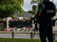 CHRISTCHURCH, NEW ZEALAND - MARCH 21: Flowers lie by the wall of Al Noor mosque as an armed policeman guards nearby on March 21, 2019 in Christchurch, New Zealand. 50 people were killed, and dozens are still injured in hospital after a gunman opened fire on two Christchurch mosques on …
