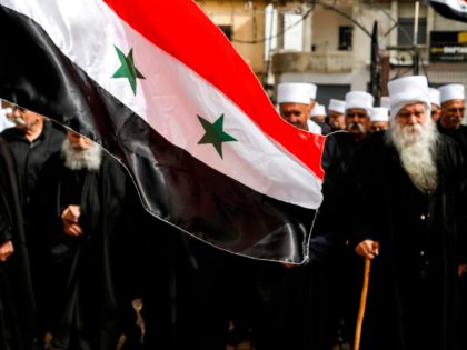 A Syrian national flag is seen before elderly Druze men attending a protest against US President Donald Trump's recognition of Israel's annexation of the Golan Heights, in the Druze village of Buqata in the Israeli-annexed territory on March 30, 2019. (Photo by JALAA MAREY / AFP) (Photo credit should read …