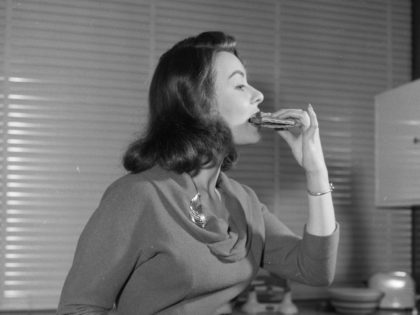 April 1958: British film actress Anne Heywood tasting a low calorie vegetarian hamburger made with breadcrumbs, walnuts, cheese and carrots. (Photo by Ken Harding/BIPs/Getty Images)