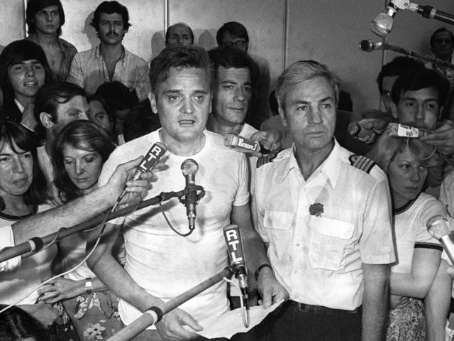 Michel Bacos (D), le commandant de bord de l'Airbus détourné par sept pirates de l'air, et l'un des 14 otages français parmi les 104 otages retenus pendant une semaine sur l'aéroport ougandais d'Entebbe, répondent à la presse à leur arrivée à Paris le 05 juillet 1976. Le reste des otages, …