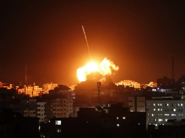 TOPSHOT - A ball of fire lights the sky above a building believed to house the offices of Hamas chief in Gaza, Ismail Haniyeh, during Israeli strikes on the Gaza City, on March 25, 2019. - Israel's military launched strikes on Hamas targets in the Gaza Strip today, the army …