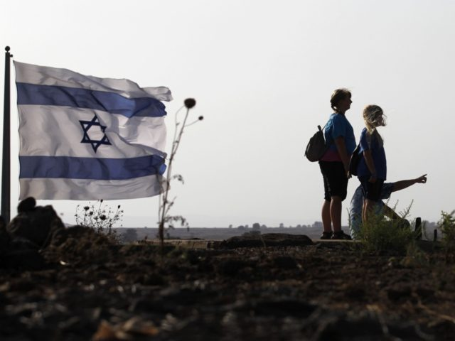 A picture taken on July 24, 2018 at the Tal Saki hill in the Israeli-annexed Golan Heights shows Israelis looking across the border onto Syria during air strikes backing a Syrian-government-led offensive in the southwestern province of Daraa. (Photo by JALAA MAREY / AFP) (Photo credit should read JALAA MAREY/AFP/Getty …