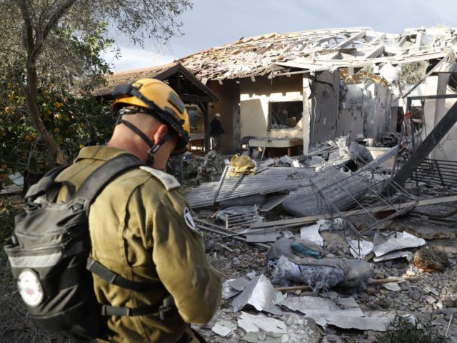 A general view shows an emergency responder inspecting a damaged house after it was hit by a rocket in the village of Mishmeret, north of Tel Aviv on March 25, 2019. - A rocket hit a house in a community north of Tel Aviv and caused it to catch fire …