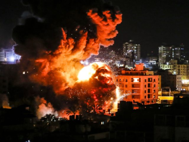 TOPSHOT - Fire and smoke billow above buildings in Gaza City during reported Israeli strikes on March 25, 2019. - Israel's military launched strikes on Hamas targets in the Gaza Strip today, the army and witnesses said, hours after a rocket from the Palestinian enclave hit a house and wounded …