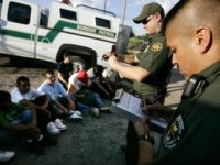 NOGALES, AZ - AUGUST 30: U.S. Border Patrol agents, David Macias (R) and Kurt Dannawitz, process a group of illegal aliens August 30, 2005 in Nogales, Arizona. The governors of New Mexico and Arizona have declared a state of emergency along the border due to drug trafficking, illegal immigration and …