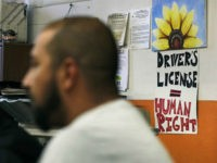 "Activists gather, with a sign stating ""Drivers License = Human Right"" on the wall, during a community meeting at the Olneyville Neighborhood Association, Tuesday, Sept. 20, 2016, in Providence, Rhode Island. Immigrant activists are planning a church-to-church march through a cluster of Rhode Island cities in response to years of …"