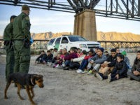 A group of about 30 Brazilian migrants, who had just crossed the border, sit on the ground near US Border Patrol agents, on the property of Jeff Allen, who used to run a brick factory near Mt. Christo Rey on the US-Mexico border in Sunland Park, New Mexico on March …