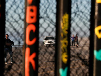 A U.S. border patrol car and tourists are seen in Imperial Beach, Calif., through the U.S. border fence from Tijuana, Mexico, Saturday, Dec. 8, 2018. (AP Photo/Rebecca Blackwell)