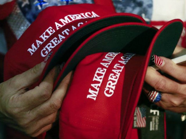 "In this June 2, 2016, file photo, a woman holds hats to get them autographed by Republican presidential candidate Donald Trump during a rally in San Jose, Calif. Trump's ""Make America Great Again"" hats proudly tout they are ""Made in USA."" Not necessarily always the case, an Associated Press review …"