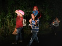 A man carries a child on his shoulders as Honduran migrants, part of the second caravan to the United States, leave San Pedro Sula, 180 km north of Tegucigalpa, on January 14, 2019. - President Donald Trump is threatening to declare a national emergency as he pressures Congress for money …