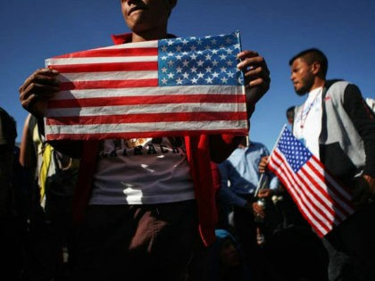 TIJUANA, MEXICO - NOVEMBER 25: Migrants hold American flags during a peaceful march shortly before some evaded a police blockade and rushed toward the El Chaparral port of entry on November 25, 2018 in Tijuana, Mexico. U.S. Customs and Border Protection temporarily closed the two ports of entry on the …