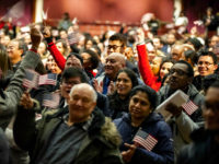 Newly sworn in US citizens celebrate and wave US flags during a naturalization ceremony at the Lowell Auditorium, where 633 immigrants became US citizens on January 22, 2019 in Lowell, Massachusetts. (Photo by Joseph PREZIOSO / AFP) (Photo credit should read JOSEPH PREZIOSO/AFP/Getty Images)