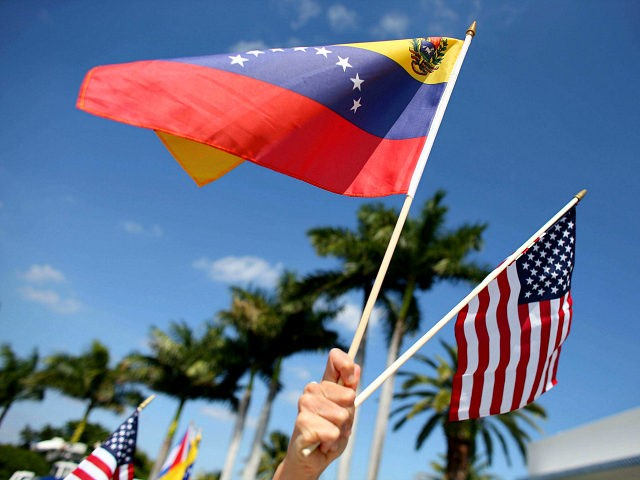 MIAMI, FL - MARCH 01: A protester holds a Venezuelan and American flag as she and other Venezuelans and their supporters show their support for the anti-government protests in Venezuela on March 1, 2014 in Miami, Florida. In Venezuela, protests over the past couple of weeks have resulted in violence …