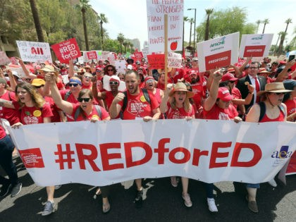 Thousands of Arizona teachers march through downtown Phoenix on their way to the State Capitol as part of a rally for the #REDforED movement on April 26, 2018 in Phoenix, Arizona. Teachers state-wide staged a walkout strike on Thursday in support of better wages and state funding for public schools. …
