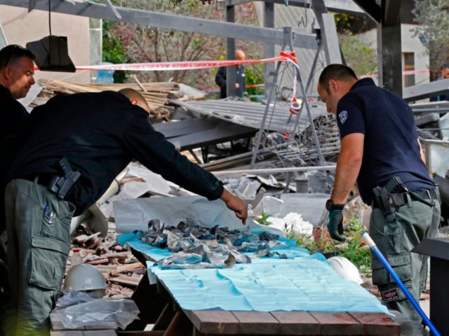 A general view shows emergency responders gathering fragments during their inspection of a damaged house after it was hit by a rocket in the village of Mishmeret, north of Tel Aviv on March 25, 2019. - A rocket hit a house in a community north of Tel Aviv and caused …