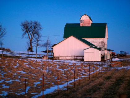 A painting of an American flag is seen on a barn at dusk near Polk City, Iowa, Sunday, Jan. 17, 2016. (AP Photo/Patrick Semansky)