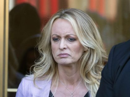 Adult film actress Stormy Daniels, left, stands with security personnel as she leaves federal court, Monday, April 16, 2018, in New York. (AP Photo/Mary Altaffer)