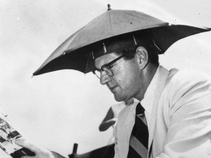 Warren Mitchell, a representative of Pan American Airways, wearing a small umbrella on his head while watching a Davis Cup match between Australia and the USA at White City tennis courts, Sydney. (Photo by Keystone/Getty Images)