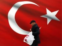 A man walks by a giant Turkish flag in Ankara, Turkey, Sunday, March 31, 2019. Turkish citizens have begun casting votes in municipal elections for mayors, local assembly representatives and neighborhood or village administrators that are seen as a barometer of Erdogan's popularity amid a sharp economic downturn. (AP Photo/Ali …