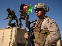 A US Marine looks on, in August 2017, as Afghan National Army soldiers raise Afghanistan's flag during a training exercise