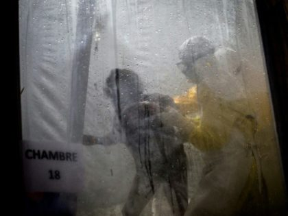 Health workers help a patient into her bed at an Ebola treatment centre in Butembo. The seven-month-old epidemic has claimed 561 lives, according to the health ministry