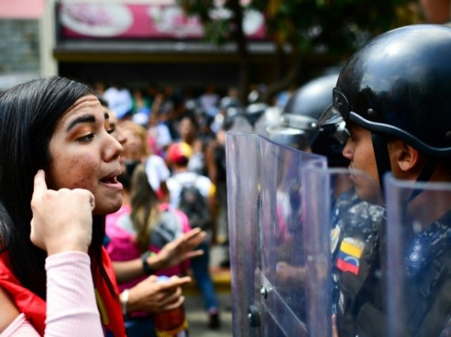 A supporter of opposition leader Juan Guaido speaks with riot police during a protest in Caracas on March 9, 2019