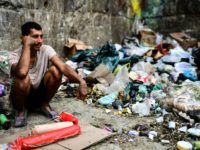 A man waits to get some food at a garbage dump in Las Minas de Baruta neighborhood, Caracas, Venezuela, on March 14, 2019