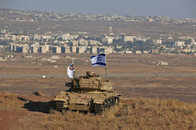 An Israeli flag flutters over the wreckage of an Israeli tank overlooking the armistice line on the Golan Heights