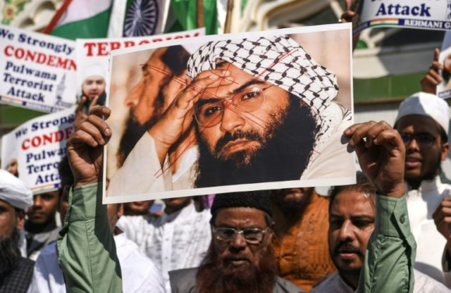 Indian Muslims hold a photo of Jaish-e-Mohammad leader Masood Azhar during a protest in Mumbai after an attack on Indian police in Kashmir