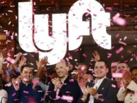 Confetti falls as Lyft CEO Logan Green (C) and President John Zimmer (left C) ring the Nasdaq opening bell celebrating the company's initial public offering on March 29, 2019