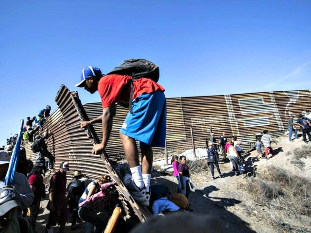 A group of Central American migrants -- mostly Hondurans -- climb a metal barrier on the U.S.-Mexico border in Tijuana. (PEDRO PARDO / AFP/Getty Images) 1 / 10