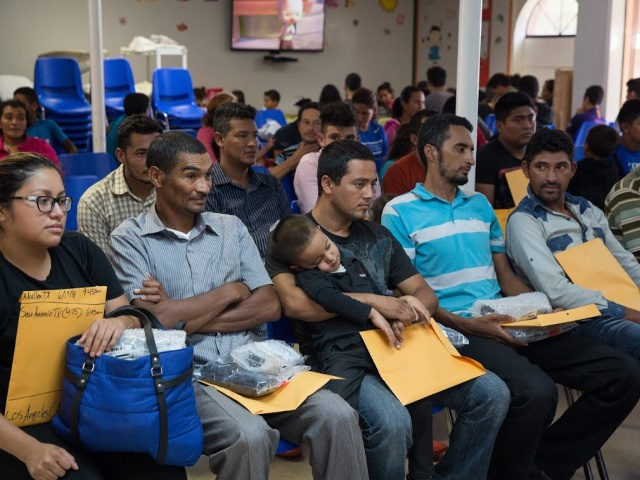 Immigrants wait for assistance with travel plans after being released from detention through the 'catch and release' immigration policy at a Catholic Charities relief centre on June 17, 2018 in McAllen, Texas. - They said they were separated for approximately six days while in detention. 'Catch and release' is a …