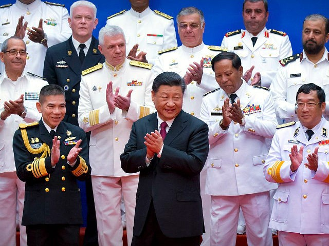Chinese President Xi Jinping, front row center, and foreign naval officials applaud after a group photo during an event to commemorate the 70th anniversary of the Chinese People's Liberation Army (PLA) Navy in Qingdao in eastern China's Shandong Province, Tuesday, April 23, 2019. (AP Photo/Mark Schiefelbein, Pool)