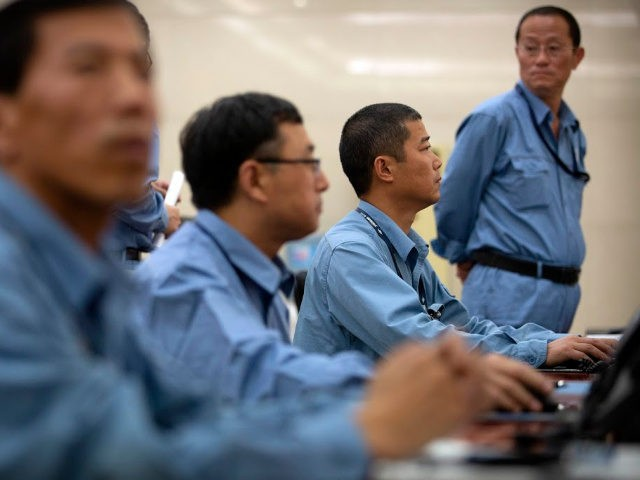 Workers sit at computer terminals as they monitor a large display screen in the command center at the Sinopec Yanshan Petrochemical Company on the outskirts of Beijing, Friday, May 25, 2018. The facility, part of the Chinese state-owned oil giant Sinopec, opened its doors to journalists on Friday as the …