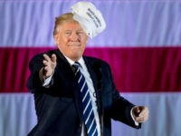 In this Friday, Dec. 9, 2016, file photo, President-elect Donald Trump throws a hat into the audience while speaking at a rally in a DOW Chemical Hanger at Baton Rouge Metropolitan Airport, in Baton Rouge, La.