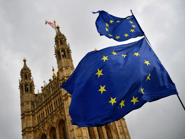 EU flags held by demonstrators flutter as the Union flag flies atop the Houses of Parliament in central London on April 4, 2019. in central London on April 4, 2019. - Britain's government redoubled its efforts Thursday to win over the main opposition party in a last-gasp bid to avoid …