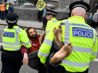 British police officers carry an activist as they remove them from Waterloo Bridge on the second day of an environmental protest by the Extinction Rebellion group, in London on April 16, 2019. - Environmental protesters from the Extinction Rebellion campaign group started a programme of demonstrations designed to block five …