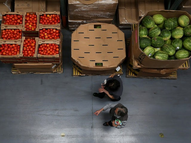 SAN FRANCISCO, CA - MAY 01: Volunteers walk by boxes of tomatoes and watermelons at the SF-Marin Food Bank on May 1, 2014 in San Francisco, California. Food banks are bracing for higher food costs and an increased demand for food from the needy as food prices are skyrocketing due …