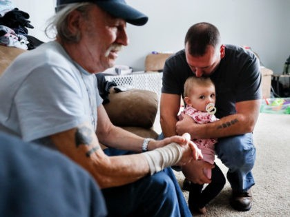 Tom Wolikow, right, holds his daughter Annabella alongside his father John, left, at their home Wednesday, Nov. 28, 2018, in Warren, Ohio. Even though unemployment is low, the economy is growing and U.S. auto sales are near historic highs, GM is cutting thousands of jobs in a major restructuring aimed …