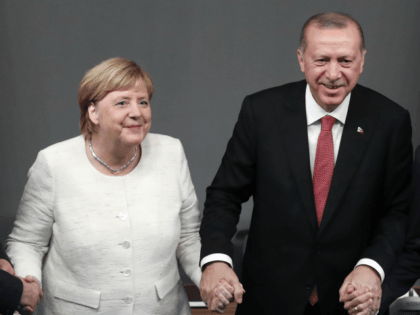 (From L) Russian President Vladimir Putin, German Chancellor Angela Merkel, Turkish President Recep Tayyip Erdogan and French President Emmanuel Macron hold hands after a conference as part of a summit called to attempt to find a lasting political solution to the civil war in Syria which has claimed in excess …