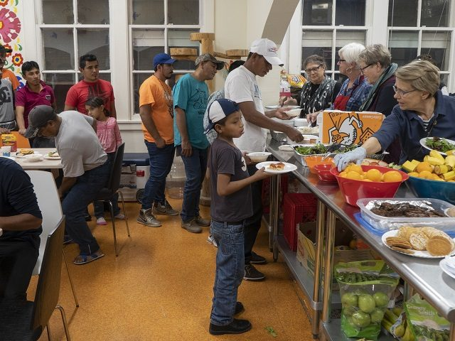Migrants receive food from volunteers at Centro San Juan Diego shelter in El Paso, Texas November 4, 2018 night, the shelter is currently housing migrants from Central America and Mexico who have sought asylum because of political instability. - Sending thousands of troops to the US-Mexico border to counter a …