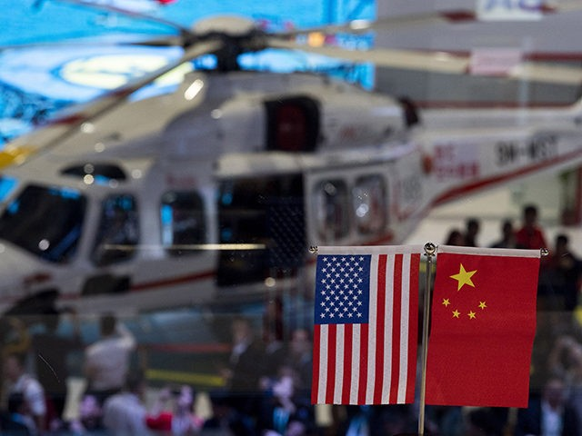 This picture taken on November 6, 2018 shows a Chinese and US flag at a booth during the first China International Import Expo (CIIE) in Shanghai. - There is a notable absentee among the dozens of national pavilions at a massive Chinese import fair -- the United States -- a …