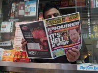 A newspaper vendor on Third Avenue in midtown New York City displays a copy of the National Enquirer for a photographer at his newstand February 8, 2019. - The publisher of the National Enquirer said Friday, February 8, 2019 it would open an internal probe of accusations by Amazon's Jeff …