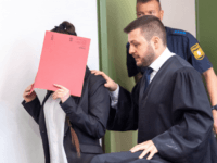 Defendant Jennifer W (L) hides her face behind a folder and walks next to her lawyer Ali Aydin (R) as she arrives at court for the opening of her trial on April 9, 2019 in Munich, southern Germany. - The German woman who joined the Islamic State (IS) jihadist group …