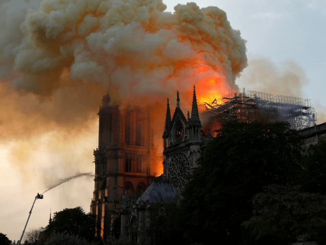 A firefighter uses a hose to douse flames and smoke billowing from the roof at Notre-Dame Cathedral in Paris on April 15, 2019. - A fire broke out at the landmark Notre-Dame Cathedral in central Paris, potentially involving renovation works being carried out at the site, the fire service said.Images …