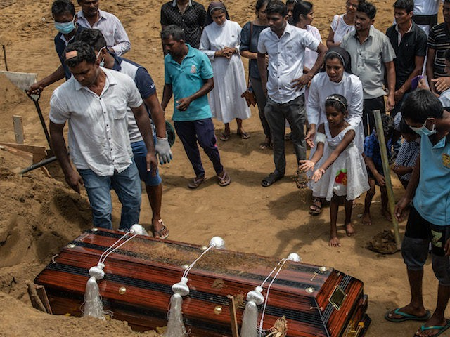 NEGOMBO, SRI LANKA - APRIL 24: A little girl throws earth on a coffin during the funeral of a person killed in the Easter Sunday attack on St Sebastian's Church, on April 24, 2019 in Negombo, Sri Lanka. At least 321 people were killed and 500 people injured after coordinated …