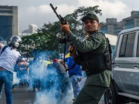 Members of the Bolivarian National Guard who joined Venezuelan opposition leader and self-proclaimed acting president Juan Guaido fire into the air to repel forces loyal to President Nicolas Maduro who arrived to disperse a demonstration near La Carlota military base in Caracas on April 30, 2019. - Guaido -- accused …