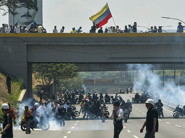 Opposition demonstrators clashes with soldiers loyal to Venezuelan President Nicolas Maduro after troops joined opposition leader Juan Guaido in his campaign to oust Maduro's government, in the surroundings of La Carlota military base in Caracas on April 30, 2019. - Guaido -- accused by the government of attempting a coup …